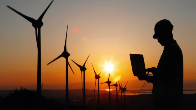 Engineer man using computer in wind turbine farm at sunset Silhouette of young male engineer holding laptop computer planning and working for the energy industry and standing beside a wind turbines farm power station at sunset time rural landscape. renewable energy stock videos & royalty-free footage