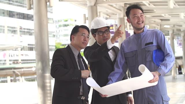 onlar inşaat alanında arıyorum yönetimi mühendislik proje tutan planı ve proje ayrıntılarını anlatılır. - güneydoğu asya stok videoları ve detay görüntü çekimi