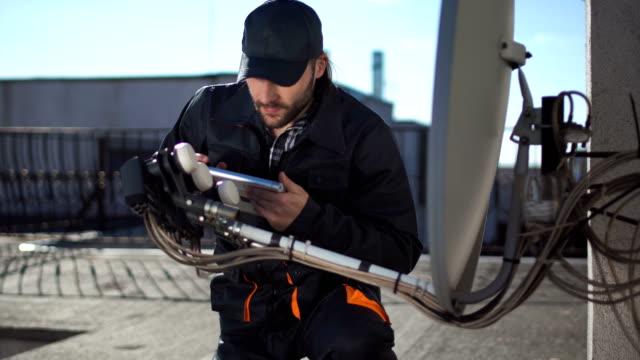 vídeos de stock, filmes e b-roll de engenheiro ou técnico de verificação uma antenas com touchpad - antena parabólica