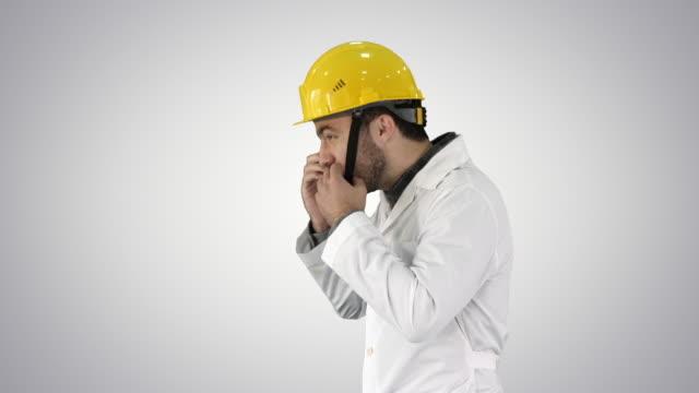 ingenieur oder arbeiter yellow safety helm hut auf head auf gradienten-hintergrund - geköpft stock-videos und b-roll-filmmaterial