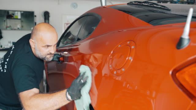 ingenieur poliert auto mit auto-polier in auto-werkstatt - wachs epilation stock-videos und b-roll-filmmaterial