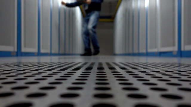 Engineer running and examining in server room