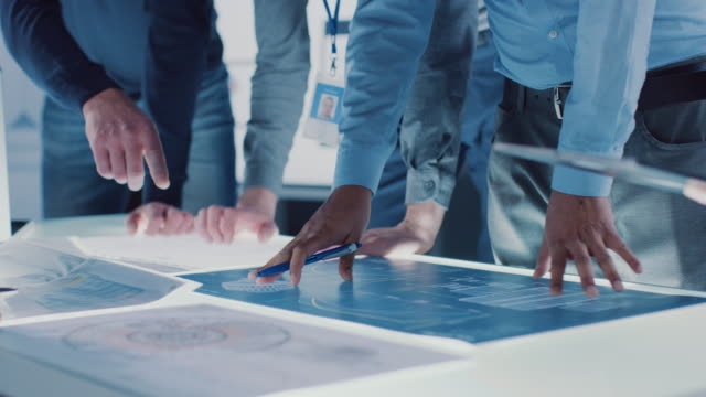 engineer, scientists and developers gathered around illuminated conference table in technology research center, talking, finding solution and analysing industrial engine design. close-up hands shot - rozwiązanie filmów i materiałów b-roll