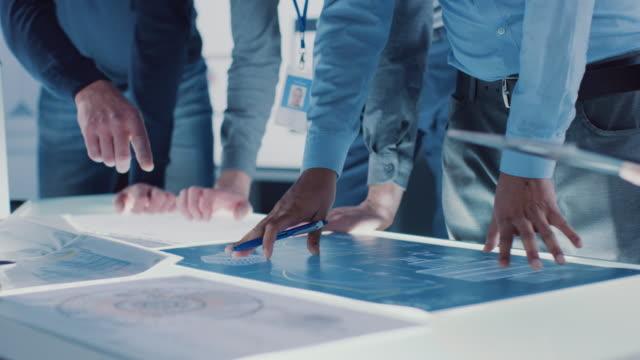 vídeos y material grabado en eventos de stock de ingeniero, científicos y promotores reunidos alrededor de la mesa iluminada de la conferencia en el centro de investigación tecnológica, hablando, encontrando solución y analizando el diseño de motores industriales. plano de las manos shot - collaboration
