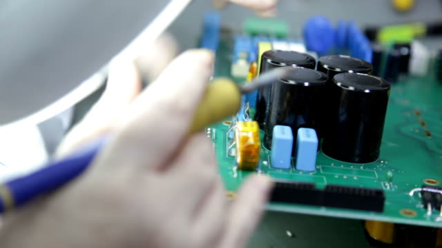 Engineer soldering circuit board with capacitor video