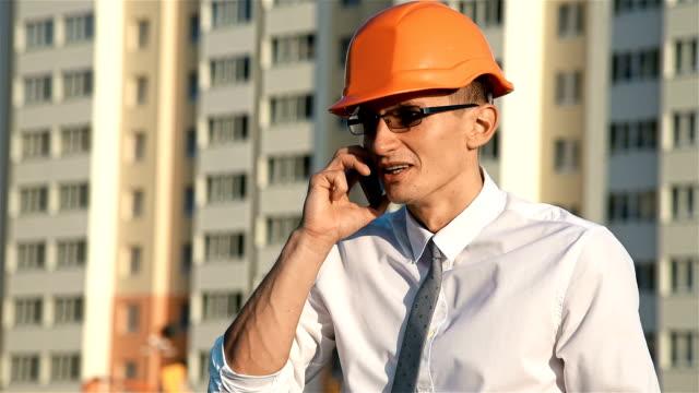 vídeos de stock e filmes b-roll de engineer speaks on smartphone - trabalho de design