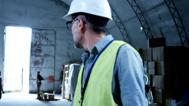 ingenieur überwacht einen roboter in einem lager - unterordnung stock-videos und b-roll-filmmaterial