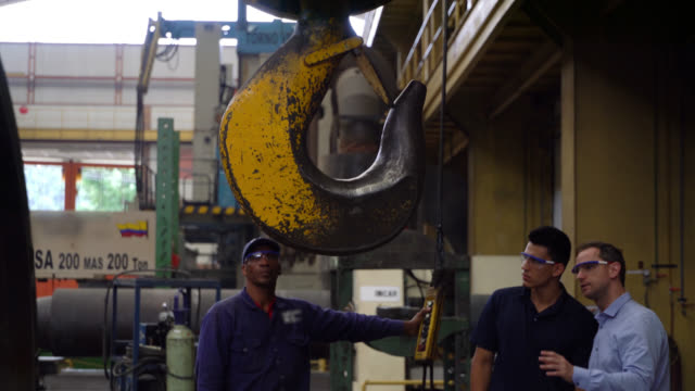 Engineer supervising operators at a metallurgic factory one operating a crane while talking to another employee