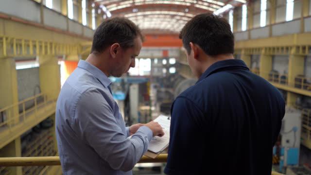 vidéos et rushes de ingénieur parlant à l'opérateur à une usine métallurgique regardant le presse-papiers tout en pointant loin - bloc note