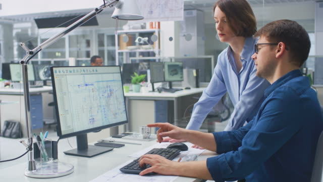Video Engineer Talking With Project Manager and Working on Desktop Computer Using CAD Software with Technical Drawings on the Screen. In the Background Engineering Facility Specialising on Industrial Design