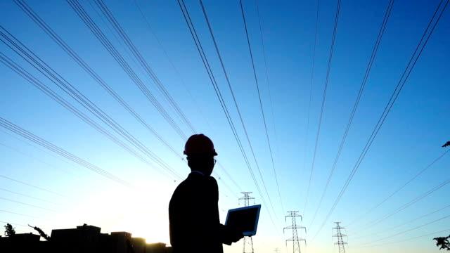 Engineer using laptop at sunset Engineer using laptop at sunset power supply stock videos & royalty-free footage