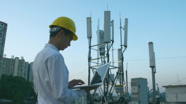 Engineer using laptop check 5G telecommunications base station tower