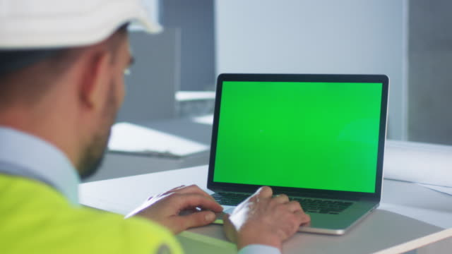 engineer using laptop computer with green screen inside building under construction. great for mockup usage. - engineer stock videos and b-roll footage