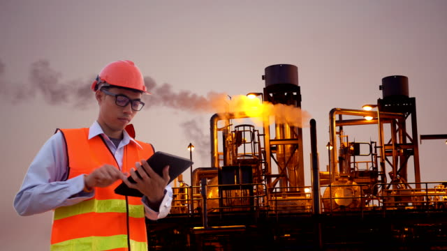 Engineer using tablet at industrial, oil or gas plant.