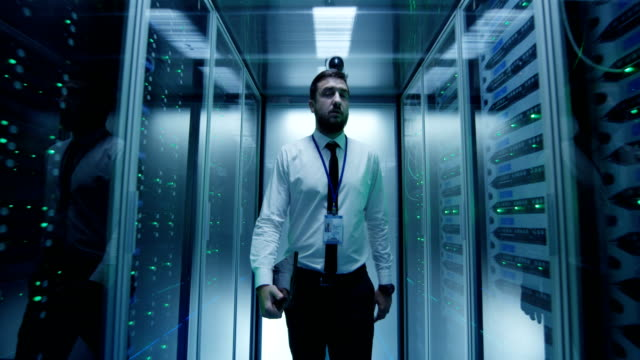 Engineer walking among server racks Formal man working in data center and walking in corridor with server racks in lights it professional stock videos & royalty-free footage