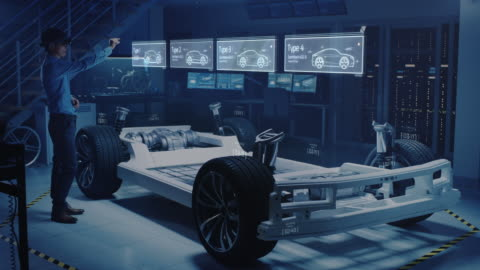 vídeos de stock e filmes b-roll de engineer wearing augmented reality headset chooses body for new electric car concept. 3d graphics visualization shows vehicle frame developing in real time into realistic concept - futurista