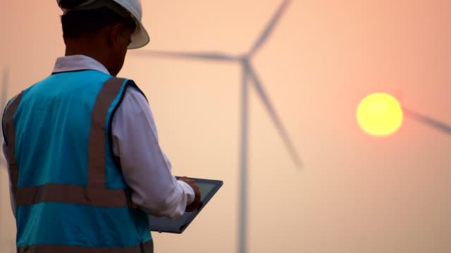 vídeos y material grabado en eventos de stock de ingeniero con tableta digital delante de turbinas eólicas al atardecer - generadores