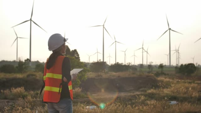 engineer with digital tablet in wind turbines farm - turbina a vento video stock e b–roll