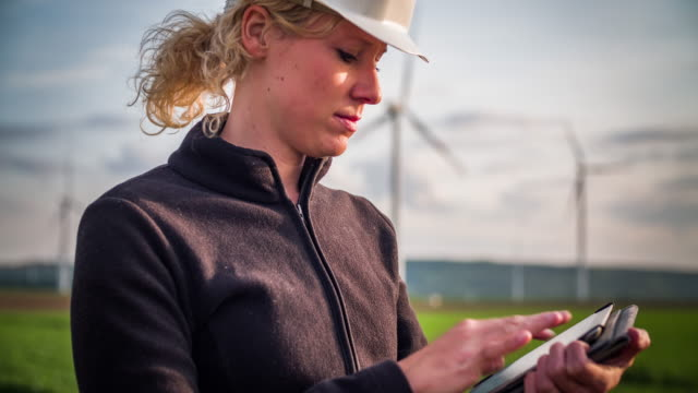 Engineer with digital tablet inspecting Wind Turbines - Women in STEM Female engineer with safety helmet working on a digital tablet in front of a wind turbine park. Clean renewable green wind power concept. turbine stock videos & royalty-free footage