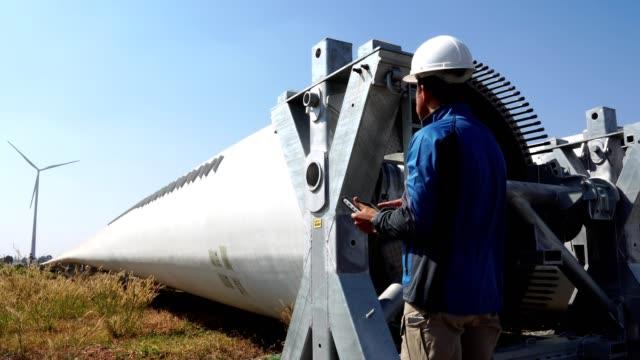 ingenjör med hård hatt mot vindturbin - vindsnurra jordbruksbyggnad bildbanksvideor och videomaterial från bakom kulisserna