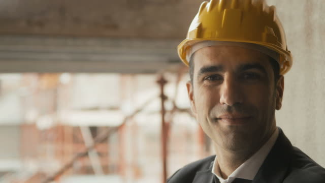 Engineer with helmet in construction site smiling at camera, portrait video
