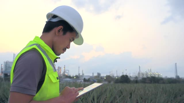 Engineer with tablet at industrial oil or gas refinery background