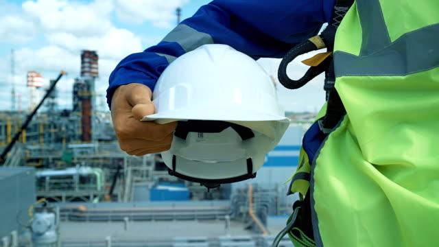 ingenieur mit weißen helm. industrial hintergrund mit blauer himmel - bauarbeiterhelm stock-videos und b-roll-filmmaterial