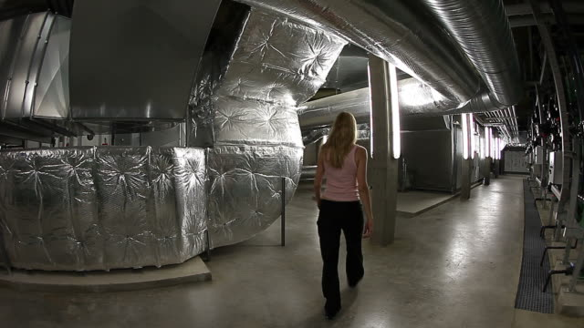 Engineer woman inspecting the underground of a big technical plant