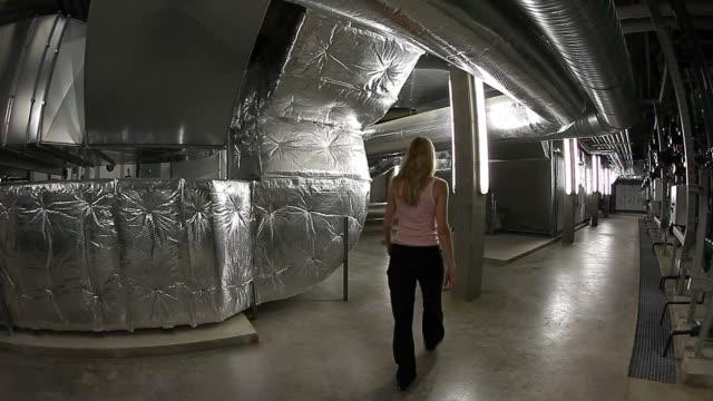 engineer woman inspecting the underground of a big technical plant - kvinna ventilationssystem bildbanksvideor och videomaterial från bakom kulisserna