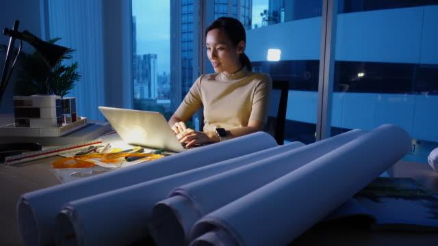 ingenjör kvinna som arbetar på hennes kontor på natten - man architect computer bildbanksvideor och videomaterial från bakom kulisserna