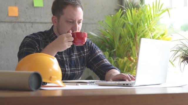 ingenjören arbete i office och dricka kaffe - man architect computer bildbanksvideor och videomaterial från bakom kulisserna