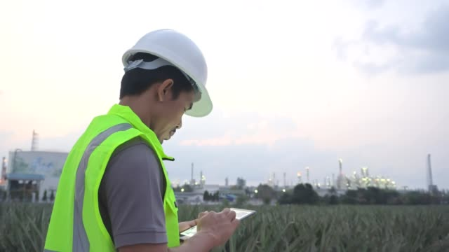 Engineer Worker at industrial plant working on a Digital tablet, oil or gas plant.