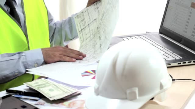 Masa başında çalışan mühendis raporları inceleyerek. video