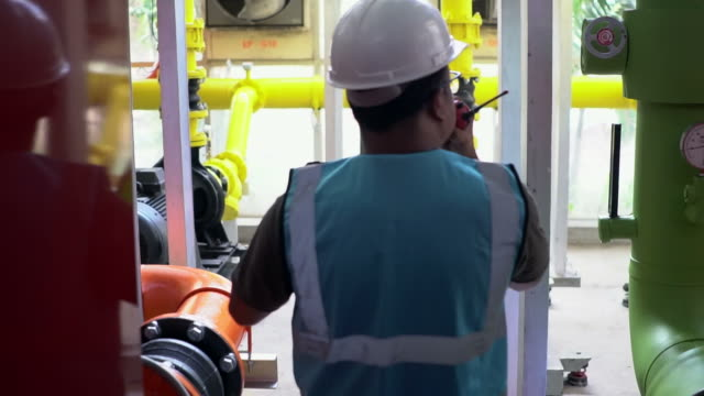 Engineer Working at Power Plant Engineer working at Power Plant near corn farm. gas pipe stock videos & royalty-free footage