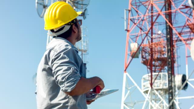 hd dolly: ingenjör som arbetar på telekommunikation tornet på platsen. - telecom bildbanksvideor och videomaterial från bakom kulisserna