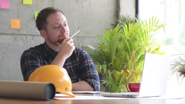 エンジニア、プロジェクトに取り組んで図面と考えて - プロジェクトマネージャー点の映像素材/bロール