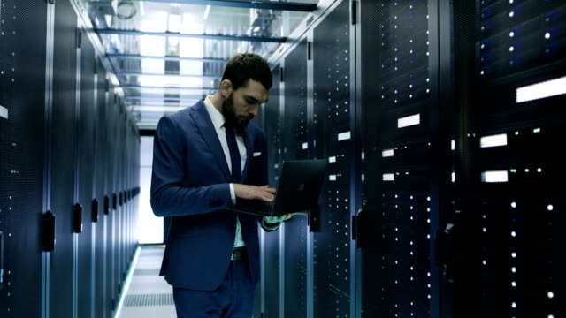 IT Engineer Working on Laptop in Data Center while Standing Before Server Rack. Running Diagnostics or Doing Maintenance Work. video