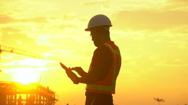 Engineer working using digital tablet in industrial plant at sun set.