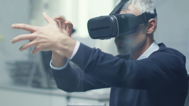 it engineer working with virtual reality headset on. he works in his modern and minimalistic office. - progettare video stock e b–roll