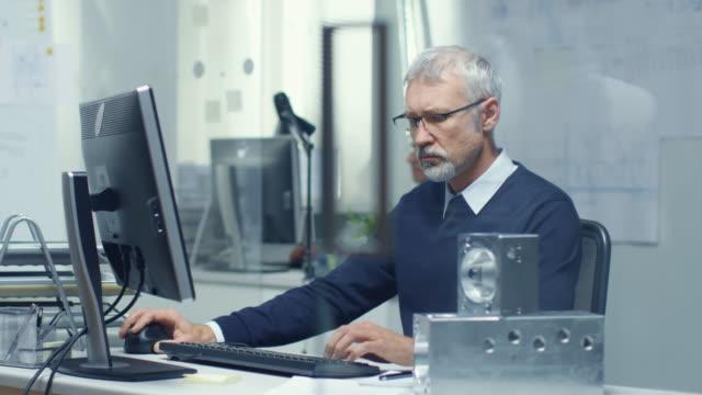 tekniska byrån. chefs ingenjör arbetar vid sitt skriv bord, några tekniska komponenter som ligger på hans skriv bord. hans assistent arbetar vid hans skriv bord i bakgrunden. - man architect computer bildbanksvideor och videomaterial från bakom kulisserna