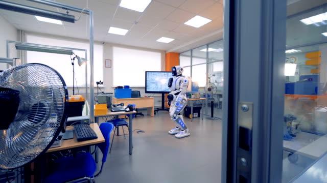 sala ufficio di ingegneria con un robot simile a un essere umano - rivoluzione industriale video stock e b–roll