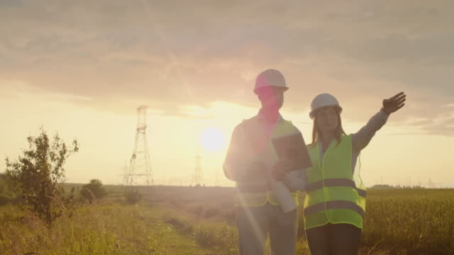 Engineering working on High-voltage tower, Check the information on the tablet computer two employees man and woman. Engineering working on High-voltage tower, Check the information on the tablet computer two employees man and woman work helmet stock videos & royalty-free footage