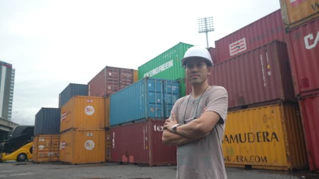 工程師年齡30-39歲,站在倉庫、倉庫和集裝箱後面,滿懷信心地交叉著。 - postal worker 個影片檔及 b 捲影像