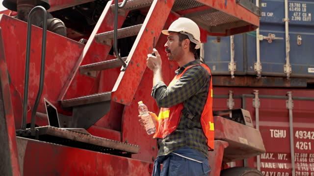 ingenieure trinken wasser aus flaschen, während sie radio verwenden, um mit dem befehl zu kommunizieren. - kopfbedeckung stock-videos und b-roll-filmmaterial