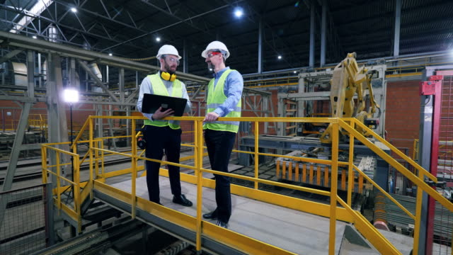 Engineers, colleagues work in a facility at a brick factory.