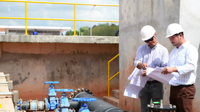 engineers discussing and talking on blueprint at construction site - acquedotto video stock e b–roll