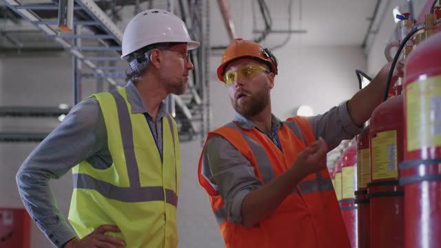 ingegneri che esaminano gli estintori della centrale elettrica - ispettore della qualità video stock e b–roll