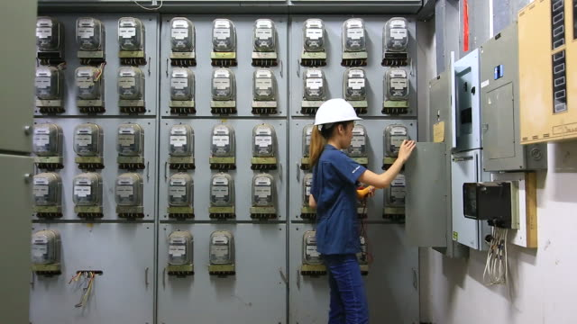 Engineers examining machinery in control room. video