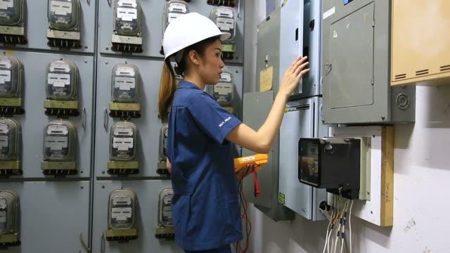Engineers examining machinery in factory