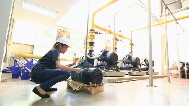 Engineers examining machinery in factory. video